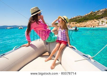 Happy mother and adorable girl enjoy vacation on boat
