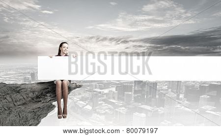 Young woman with white blank banner sitting on rock top