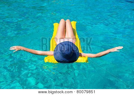 Woman relaxing on inflatable mattress in clear sea