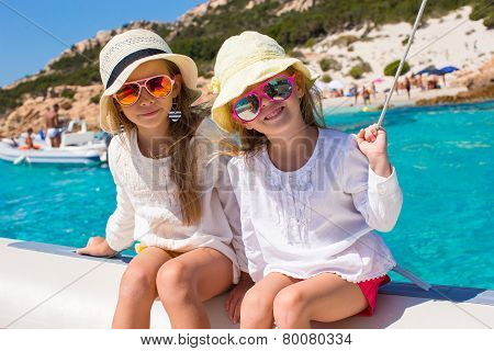 Little girls sailing on boat in clear open sea
