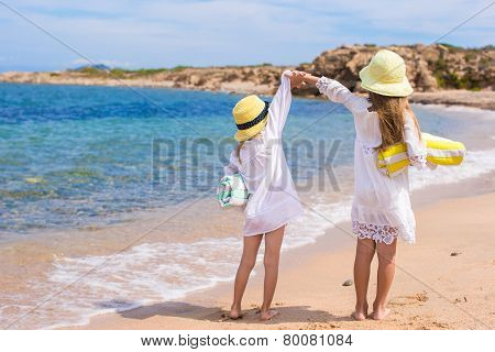 Adorable cute girls have fun on white beach during vacation