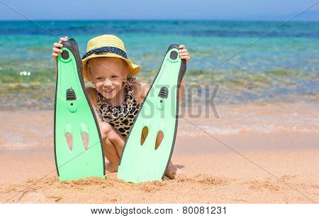 Little girl with flippers and goggles for ssnorkling on the beach