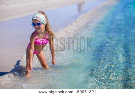 Adorable little girl have fun in shallow water at tropical beach