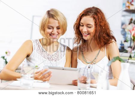 Two young ladies in cafe using tablet pc
