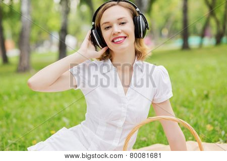 Young attractive girl in summer park wearing headphones