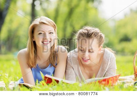 Young pretty girls in summer park reading book