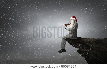 Businessman in Santa hat and beard playing violin