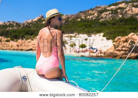 Beautiful young girl relaxing on the boat in open sea