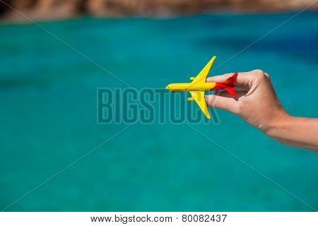 Small homemade plane in hand on background of the sea