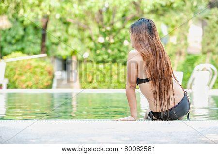 Asia Beautiful Woman In Bikini Sitting On Edge Of The Pool