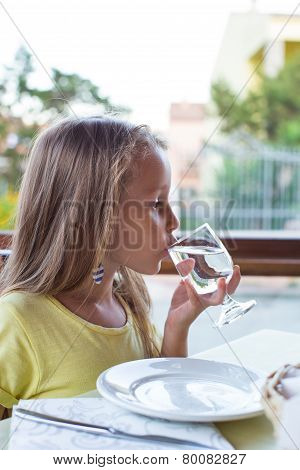 Adorable little girl having breakfast at restaurant