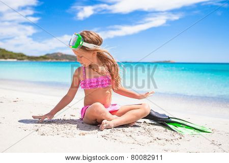 Little girl with flippers and goggles for snorkling