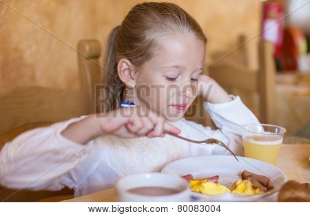 Adorable little girl having breakfast at indoor cafe