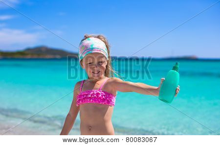 Little adorable girl in swimsuit with suntan lotion bottle
