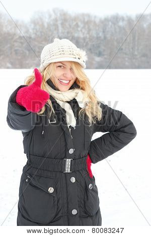 Woman In Snow Looking Up At Camera With Thumb Up Outside