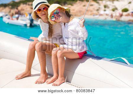 Little cute girls enjoying sailing on boat in the open sea