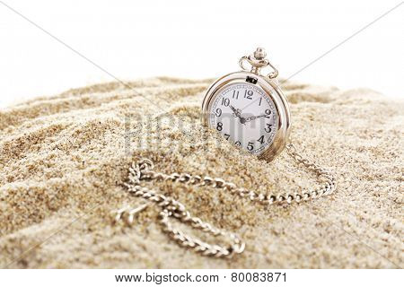 Silver pocket clock on sand isolated on white