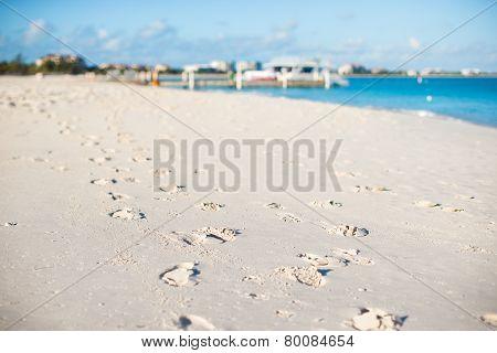 Human footprints on white sand of the Caribbean island