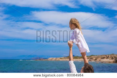 Adorable little girl and happy father during beach vacation