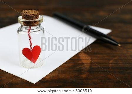 Blank sheet of paper with pen and little glass bottle with heart on rustic wooden table background