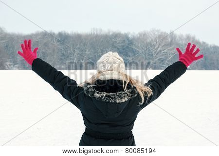 Woman In Snow Showing Her Back And Facing Forest With Hands Raised