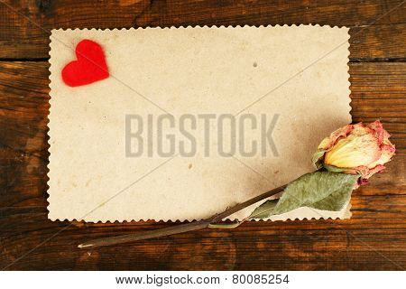 Blank sheet of paper with little hear and dried rose on wooden table background