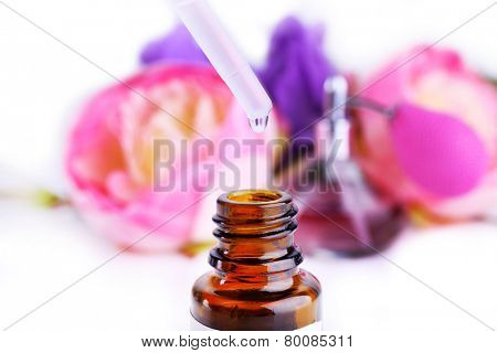 Dropper bottle of perfume with flowers on light background