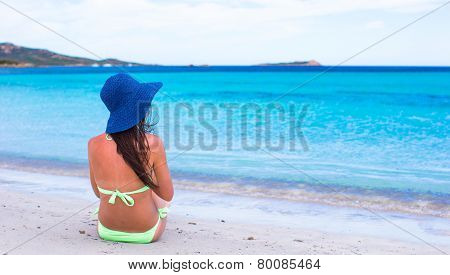 Back view of woman relaxing at tropical beach during summer vacation