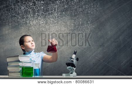 Cute school girl at chemistry lesson with test tube