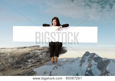 Young woman sitting on rock edge with blank banner