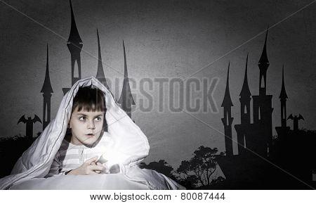 Little cute boy sitting in bed under blanket with flashlight