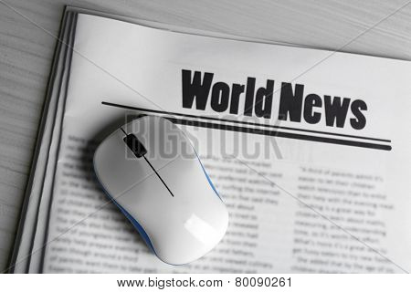 On-line news concept. Computer mouse and newspaper on wooden table background