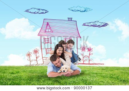 Happy family with puppy against blue sky over green field