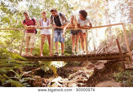 Group Of Friends On Walk Crossing Wooden Bridge In Forest