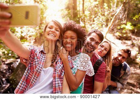 Group Of Friends On Walk Taking Selfie In Forest