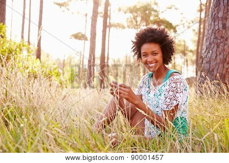 Portrait Of Smiling Young Woman Sitting In Countryside