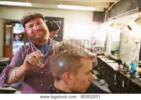 Portrait Of Male Barber Giving Client Haircut In Shop