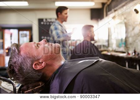 Customer Reclining In Barber's Chair Ready For Shave