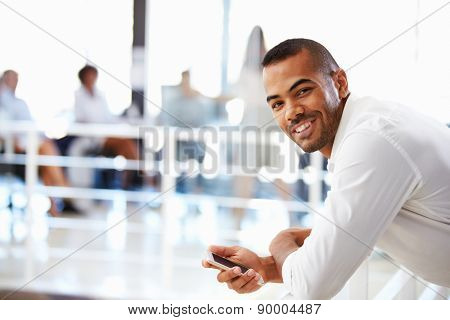 Portrait of man in office with telephone, smiling