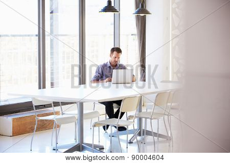 Young man working in empty meeting room
