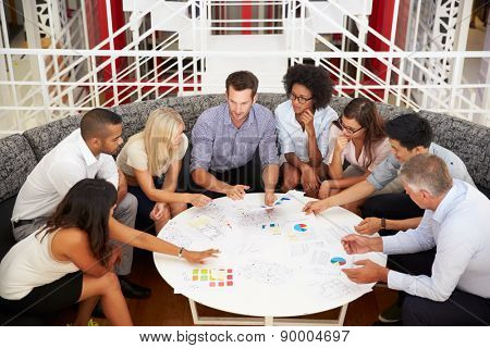 Group of work colleagues having meeting in an office lobby