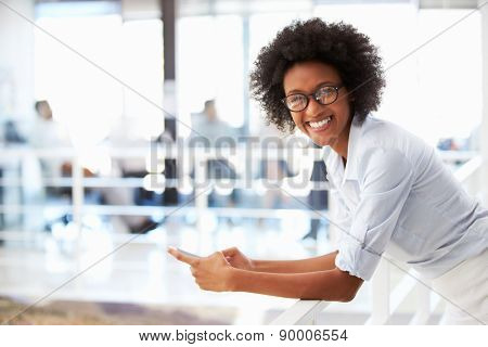 Portrait of smiling woman in office with telephone
