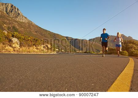 Man and woman running together on an empty road