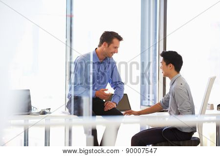 Two men talking in a modern office