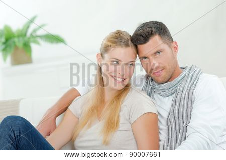 Smiling couple sat on sofa