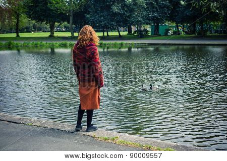 Woman Standing By Pond In A Park