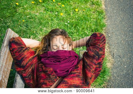 Woman Sleeping On A Bench In The Park
