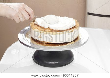 Cook spreads cream on the cake