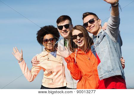 friendship, tourism, travel and people concept - group of happy teenage friends in sunglasses hugging and waving hands outdoors