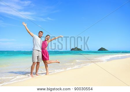 Beach vacation happy carefree couple arms raised. Winning couple with arms up showing happiness and fun on beach with pristine turquoise water on Lanikai beach, Oahu, Hawaii, USA with Mokulua Islands.